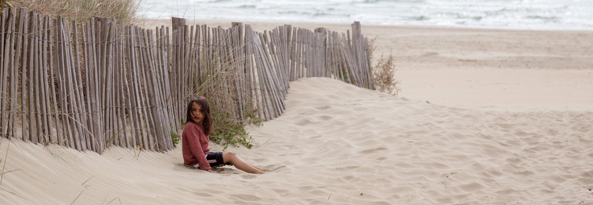 petite fille assise sur une plage vide